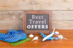 stock image of  blackboard with text & x22;best travel offers& x22;, plane, flops, seashells on brown wooden background