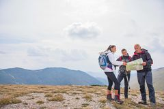 stock image of  adventure, travel, tourism, hike and people concept - group of smiling friends with backpacks and map outdoors