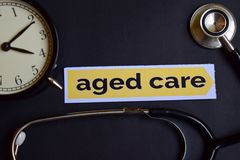 stock image of  aged care on the print paper with healthcare concept inspiration. alarm clock, black stethoscope.