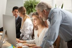stock image of  aged executive manager supervising computer work of intern in of