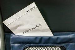 stock image of  air sickness bag tucked behind airplane seat pocket