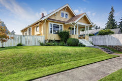 stock image of  american craftsman home with yellow exterior paint.