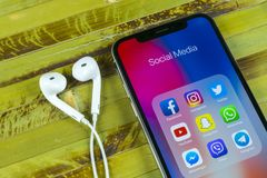 stock image of  apple iphone x with icons of social media facebook, instagram, twitter, snapchat application on screen. social media icons. social