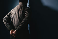 stock image of  arrested male criminal with handcuffs facing prison wall