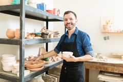 stock image of  artisan holding clay bowl by shelves in pottery workshop