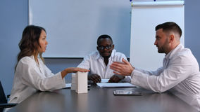 stock image of  asian female doctor presenting new pills to colleagues