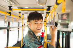 stock image of  asian man taking public transport, standing inside bus.