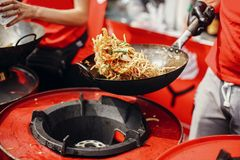 stock image of  asian street food festival in city. chef cooking noodles and vegetables in a pan on fire. fried chinese japanese noodles with