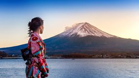 stock image of  asian woman wearing japanese traditional kimono at fuji mountain. sunset at kawaguchiko lake in japan
