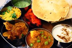 stock image of  assorted indian food set in tray, tanduri chicken, naan bread, yoghurt, traditional curry, roti