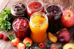 stock image of  assortment of jams, seasonal berries, plums, mint and fruits.