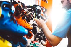 stock image of  assortment roller skates isolated in store shop, person choosing and buy color roller-skates on backgraund sun flare, healthy and