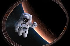 stock image of  astronaut in outer space from porthole on background of the mars. elements of this image furnished by nasa
