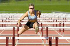 stock image of  athlete jumping over hurdles