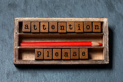 stock image of  attention please. warning note and retro style caution banner concept. vintage box, wooden cubes with old style letters