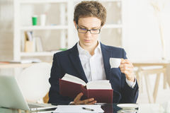stock image of  attractive businessman drinking coffee and reading book