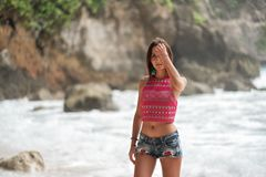stock image of  attractive woman in shorts removes hair from the face, on the background of the ocean