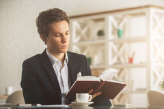 stock image of  attractive guy drinking coffee and reading book