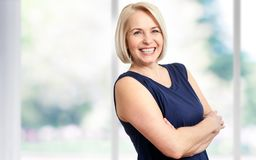 stock image of  attractive middle aged woman with a beautiful smile near the window.
