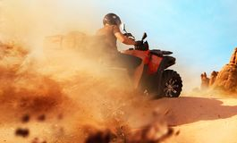 stock image of  atv riding in sand quarry, dust clouds, quad bike