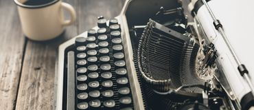 stock image of  author workplace at home concept. typewriter with paper sheet