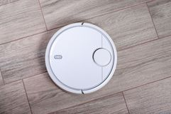 stock image of  automated robot vacuum cleaner on tile floor. smart robotic automate wireless cleaning technology housekeeping