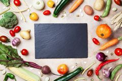 stock image of  autumn farm vegetables, root crops and slate cutting board top view with copy space for menu or recipe. healthy and organic food.