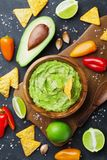 stock image of  avocado guacamole with ingredients pepper, lime and nachos on black table top view. traditional mexican food.