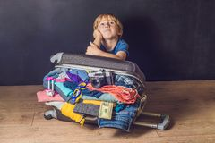 stock image of  baby boy and travel suitcase. kid and luggage packed for vacation full of clothes, child and family trip