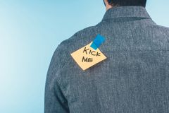 stock image of  back view of man with note on sticky tape with kick me lettering on back, april fools day