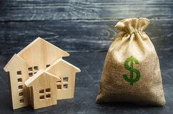 stock image of  a bag with money and wooden houses. selling a house. apartment purchase. real estate market. rental housing for rent. home prices