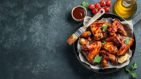 stock image of  baked chicken wings in barbecue sauce with sesame seeds and parsley in a cast iron pan on a dark concrete table. top view with