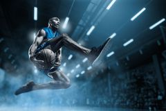 stock image of  basketball player on big professional arena during the game. basketball player making slam dunk.