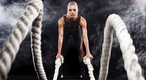 stock image of  battle ropes session. attractive young fit and toned sportswoman working out in functional training gym doing exercise