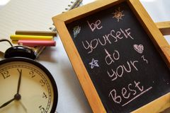 stock image of  be your best friend phrase colorful handwritten on chalkboard, alarm clock with motivation and education concepts.