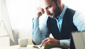 stock image of  bearded young businessman working on modern office. consultant man thinking looking in monitor computer. manager writes in noteboo