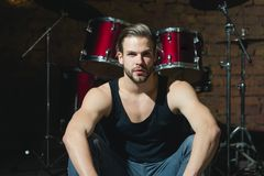 stock image of  beat of drums. rock star or rocker. enjoying instrumental music. handsome man sit on stage at percussion instrument. man