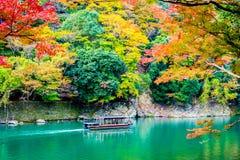 stock image of  beautiful arashiyama river with maple leaf tree and boat around lake