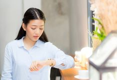 stock image of  beautiful asian young woman look at watch waiting for friend or someone.