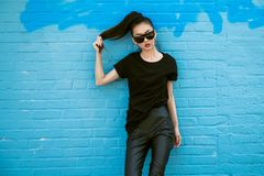 stock image of  beautiful fashionable asian girl wearing sunglasses and black clothes outfit posing in front of blue wall.