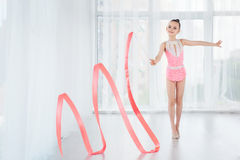 stock image of  beautiful little gymnast girl in pink sportswear dress, doing rhythmic gymnastics exercise spirals with art ribbon