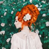 stock image of  beautiful redhead woman with high hairdo in a white dress on rose background. portrait of young unusual pale girl with red hair.