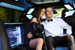 stock image of  beautiful woman in back prom dress and handsome guy in suit, teenager ready for a luxury night.