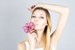 stock image of  beautiful woman with pink flower and her hand raised. waxing armpit. epilation result.