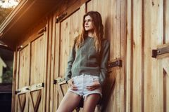 stock image of  beautiful young adult country woman posing near barn farm wooden doors at sunset time wearing white shorts and green sweater.