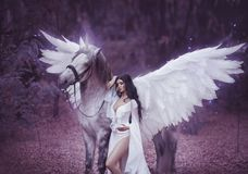 stock image of  beautiful, young elf, walking with a unicorn. she is wearing an incredible light, white dress. art hotography