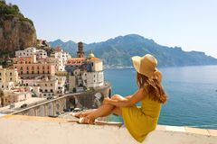 stock image of  beautiful young woman with hat sitting on wall looking at stunning panoramic village of atrani on amalfi coast, italy