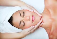 stock image of  beautiful young woman receiving facial massage.