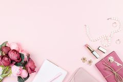 stock image of  beauty blog concept flat lay. fashion accessories, flowers, cosmetics, jewelry on pink background, copyspace.