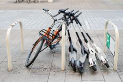 stock image of  bicycle and electric scooters parked on city street. self-service street transport rental service. rent urban vehicle